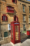 An old red cardphone booth in the historic city Valletta with an old appartment building in the background Royalty Free Stock Photos