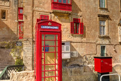 An old red cardphone booth in the historic city Valletta with an old appartment building in the background Stock Photos