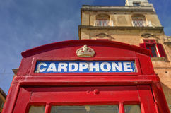 An old red cardphone booth in the historic city Valletta with an old appartment building in the background Royalty Free Stock Images