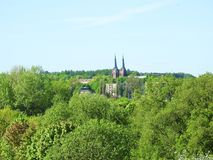 Church and green spring trees, Lithuania Stock Images