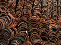 Old red ceramic roof tiles piled in a heap. Stock Image