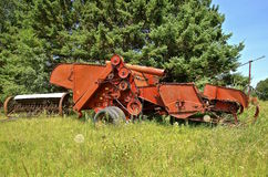 Old red combine parked in the grass Stock Photo