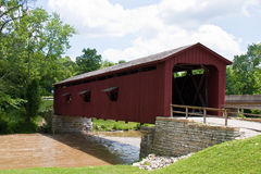 Old Red Covered Bridge Over Muddy River Royalty Free Stock Photos