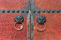 Old red cracked paint chinese traditional wooden gate with Lion Stock Photo
