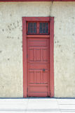 Old red door. An old red door on a grungy wall Royalty Free Stock Photos