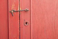 An old red door with keyhole and locking hook Stock Photography