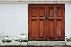 Old red door in old white wall Stock Photos