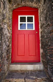 Old red door on a stone building. Stock Images