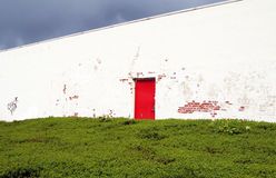 Old red door in white wall Royalty Free Stock Photo