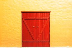 Old red door in yellow wall Stock Images