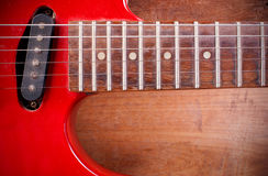 The old red electric guitar that is placed on a wooden floor. Stock Images
