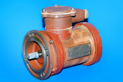 Old red electric motor isolated on a blue background Royalty Free Stock Photos