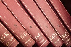 Close-up of a red old encyclopedia. An old red encyclopedia collection standing in a dust covered shelf royalty free stock images