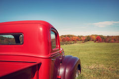 Old red farm truck against autumn landscape