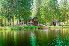 Old red Finnish summer cottage at a lake Stock Images