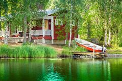 Old red Finnish summer cottage at a lake Stock Photos