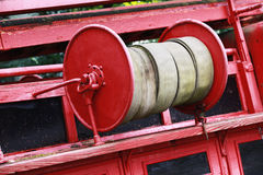 Old red fire hose reel, closeup photo Royalty Free Stock Image
