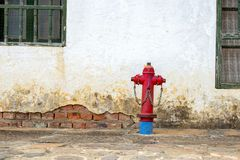 Old red fire hydrant in a stone paved street stock photo