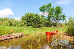 Old red fishing wooden boat at the bank of lake Stock Images