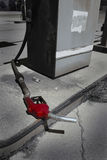 Old Red Gas Pump Handle Laying on Ground Stock Photo