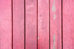 Old, red grunge wood vertical panels on a rustic barn.  Royalty Free Stock Image