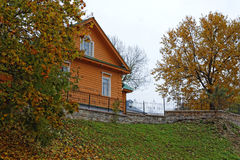 Old red house under autumn orange trees. Typical Russian landsca Royalty Free Stock Photo