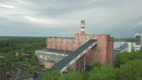 Old red industrial factory building with tall smokestack against grey rainy sky. Aerial view stock footage