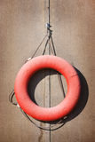 Old red lifebuoy on the wall Royalty Free Stock Photo