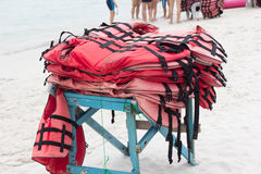 Old red lifejackets. On a table stock images