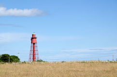 Old red lighthouse. Old red metallic lighthouse with blue sky Stock Images