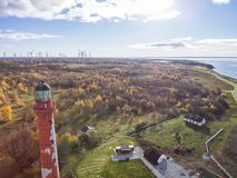 Old red Lighthouse in Paldiski, Estonia staying on a seacoast of. Baltic Sea with the green energy windmills on the background Royalty Free Stock Photos