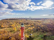 Old red Lighthouse in Paldiski, Estonia staying on a seacoast of. Baltic Sea with the green energy windmills on the background Stock Photos