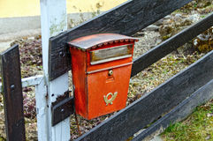 Old red mailbox on a wooden fence. Austria. Street red mailbox with the symbol of the post horn on it Royalty Free Stock Photo