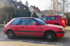 Old red Mazda 323 parked Stock Photos