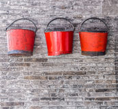 The old red metal buckets on the brick wall Stock Images