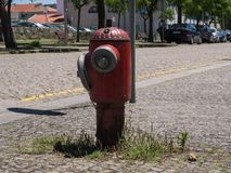 Old red metal fire hydrant in street, Vila do Conde, Porto, Portugal stock photo