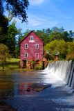 Old red mill and river dam Stock Photos
