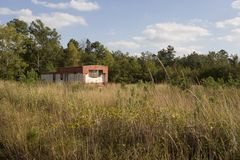 Old red mobile home. An old deserted mobile home on an overgrown field Stock Photo