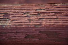 Old red paint on the piece of the wood. Old red cracked paint on the piece of the wood royalty free stock photos