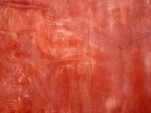 Old red painted faded stained cracked rough plaster wall background. An old red painted faded stained cracked rough plaster wall background royalty free stock photo