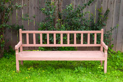 Old red park bench stands on green grass Stock Image