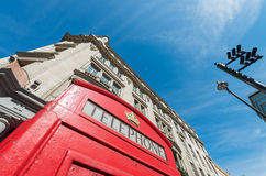 Old Red Phone Booth with London buildings on background Royalty Free Stock Photos