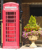 Old Red Phone Booth by Potted Plant Stock Photos