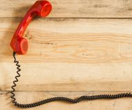 Red old fashioned telephone receiver on wooden table Royalty Free Stock Image