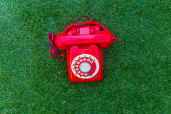 Old red phone  on the field of green grass Stock Photo