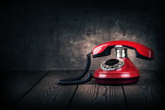 Old red phone on a wooden table. With dark background stock photos