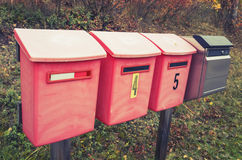 Old red post boxes on a roadside in a row Royalty Free Stock Photos
