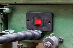 Old red power switch on a green machine for the production and industry with the words on and off in the off position. Concept of royalty free stock photos