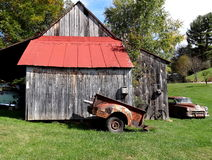Old Red Roof Barn with Old Car. Old tobacco barn with rusty vintage car, truck bed, and wagon wheel Royalty Free Stock Image