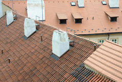 Old red rooftops with tiles and white chimneys in Prague stock photos